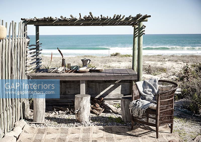 Wooden outdoor dining table overlooking sea