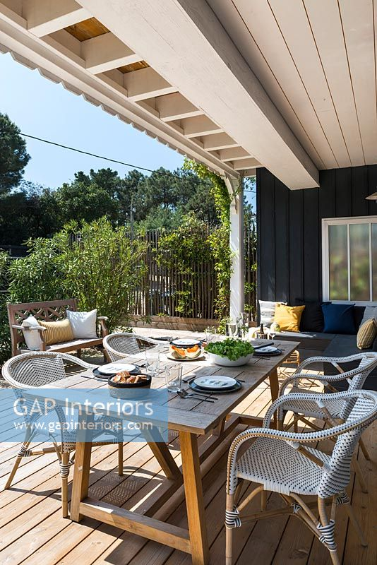 Outdoor living and dining area on decked terrace, summer