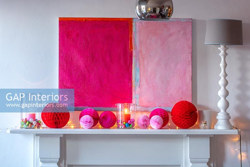 Pink modern artwork and Christmas decorations over fireplace