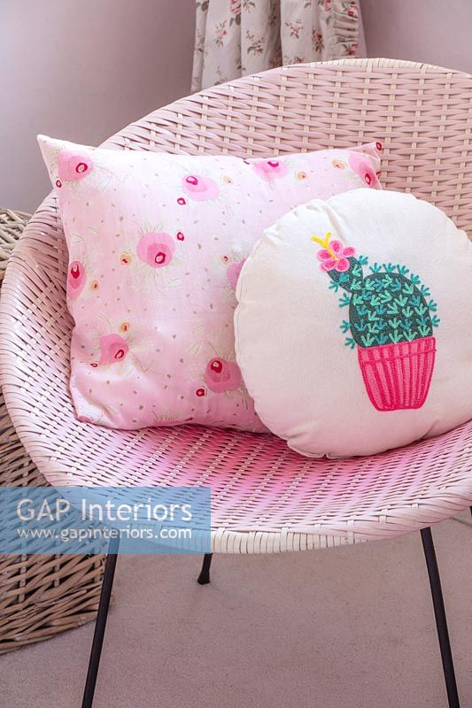 Modern patterned cushions on pink rattan chair