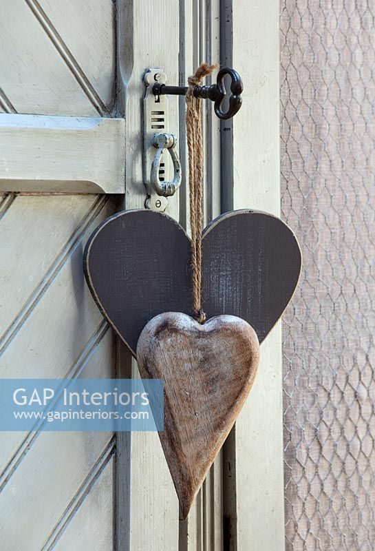Carved wooden hearts on vintage key in door