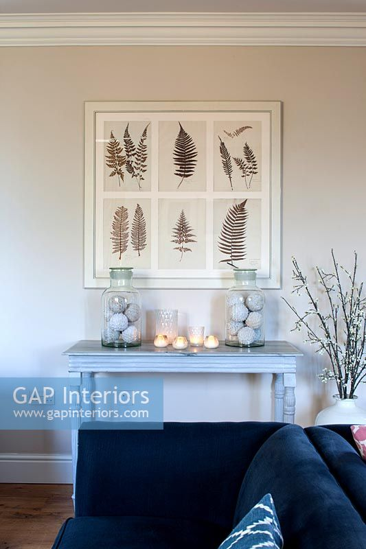 Painting of ferns above table decorated with candles