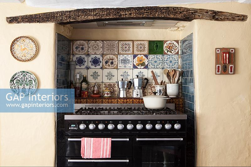 Large range cooker in country kitchen with decorative tiling