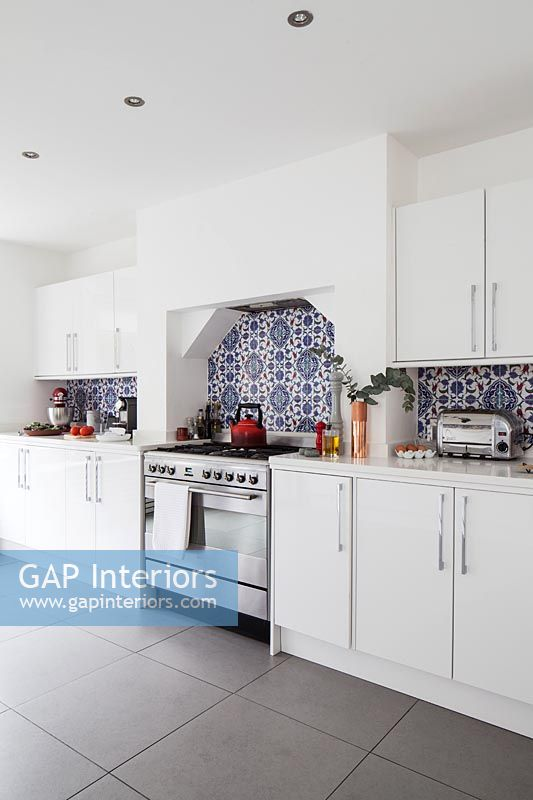 Modern white kitchen with patterned blue tiles