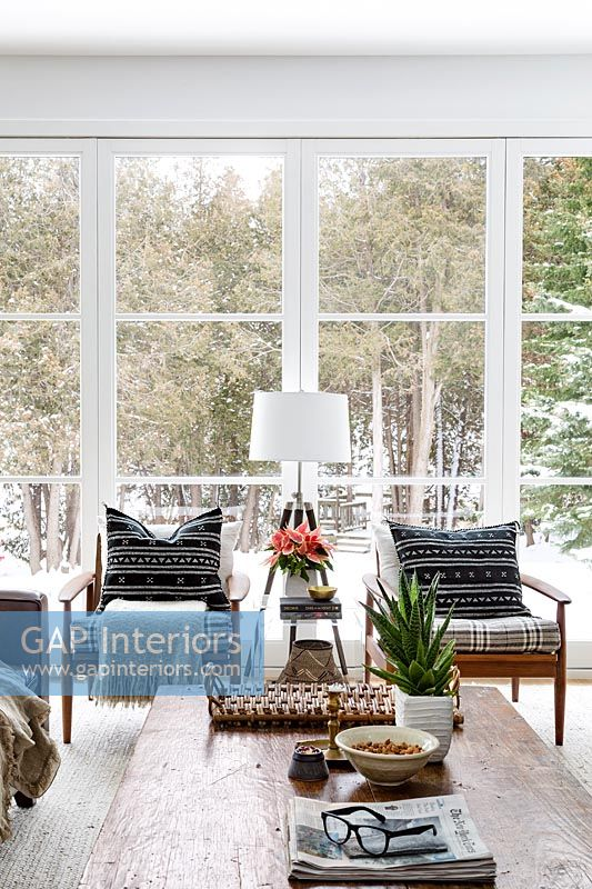 Wooden armchairs by large windows in winter