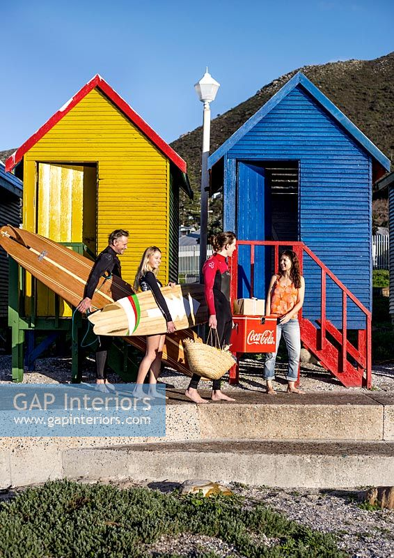 Surfers next to colourful beach huts