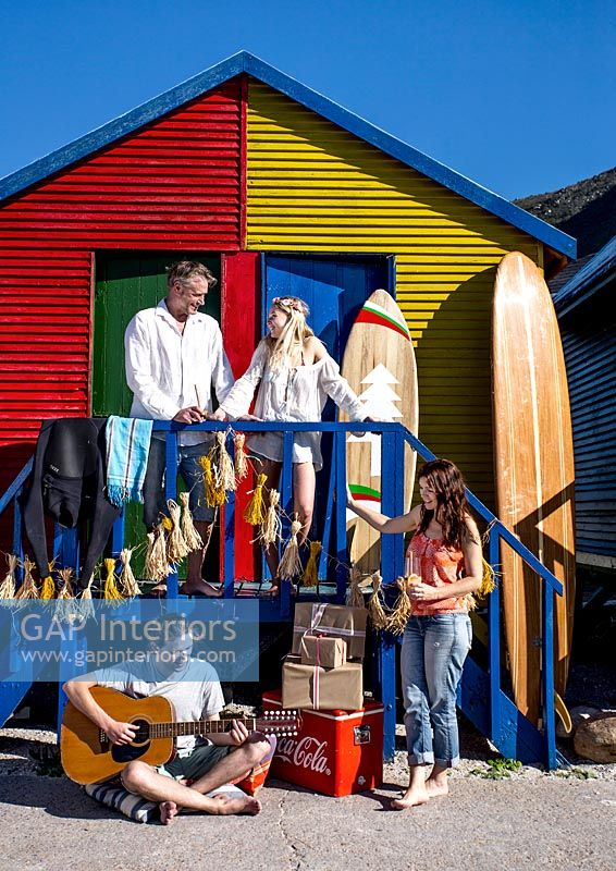 Family outside colourful beach huts
