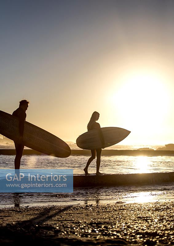 Man and woman standing on beach at sunset holding surfboards