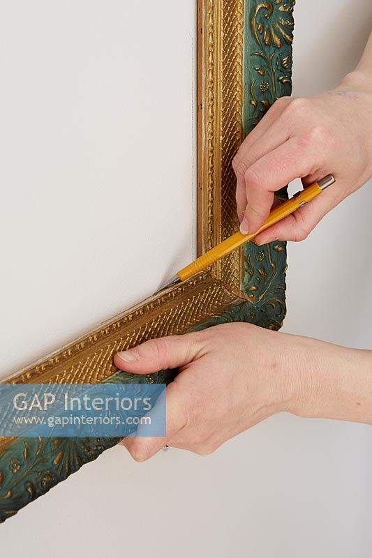 Using a pencil to mark shape of picture frame onto wall
