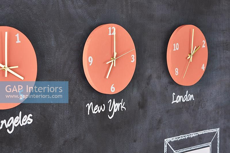 Orange wall clocks displaying different time zones on blackboard wall
