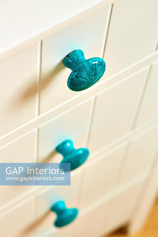 Turquoise door knobs on chest of drawers