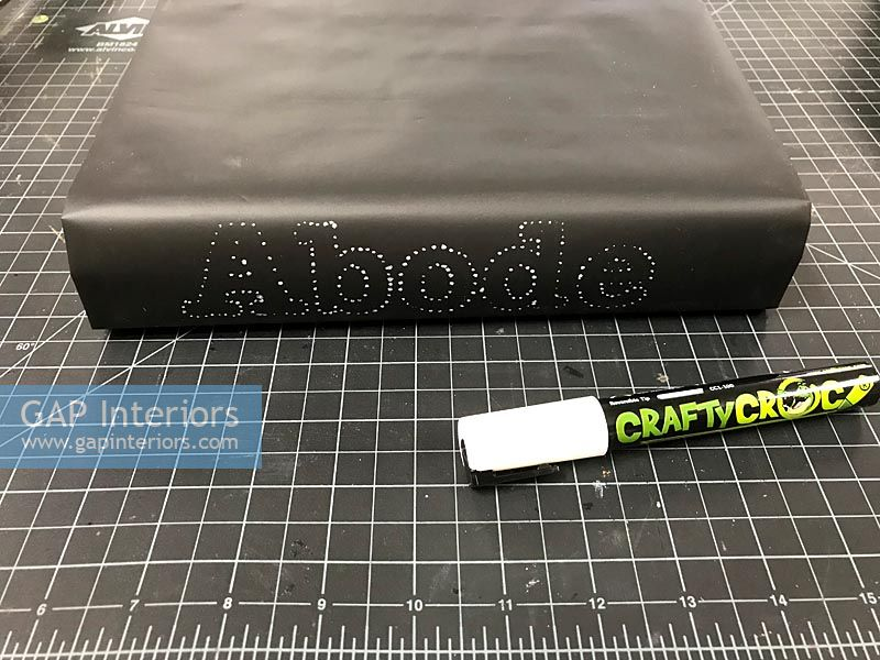 Decorated book spine - the word abode in white spots on black book
