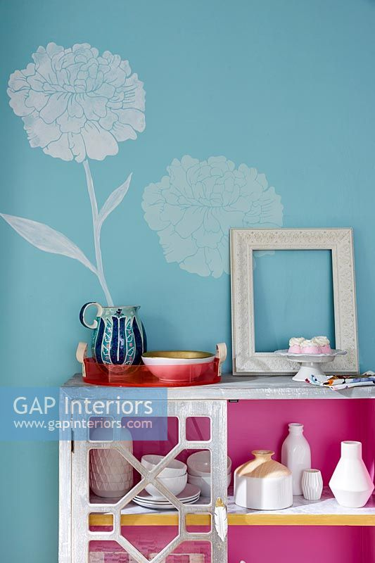 White painted flower on blue wall and pink lining inside sideboard cupboard