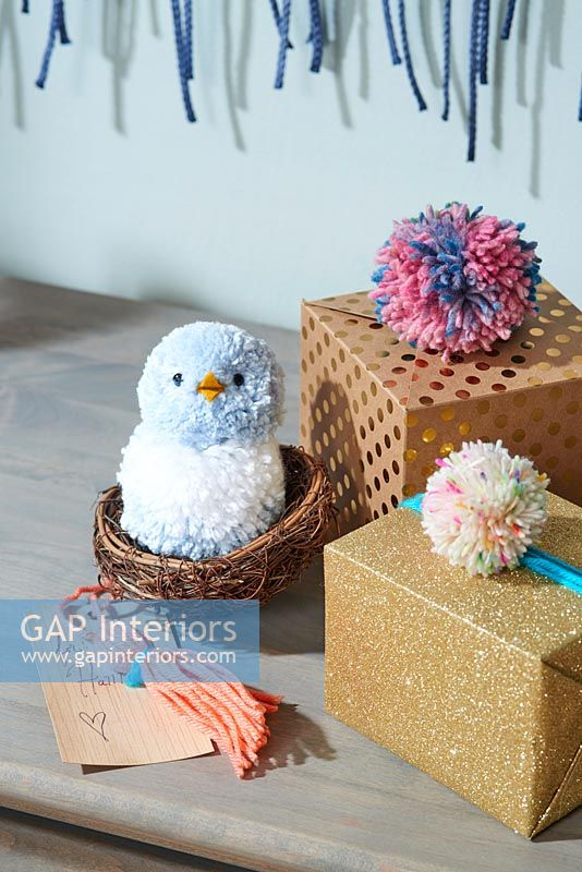 Bird made from pom poms in basket and gift decorations