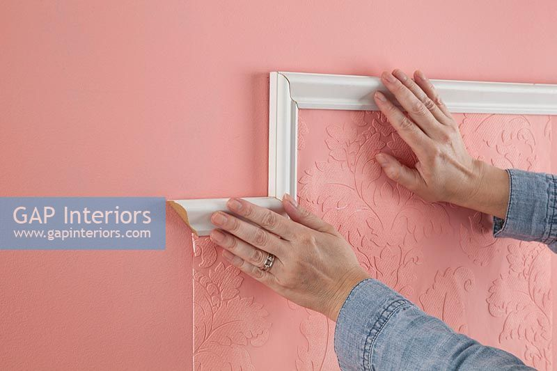 Sticking frame around section of pink embossed wallpaper