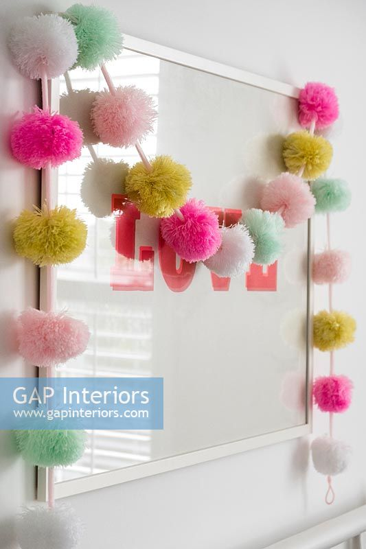 String of colourful pom-poms over framed picture