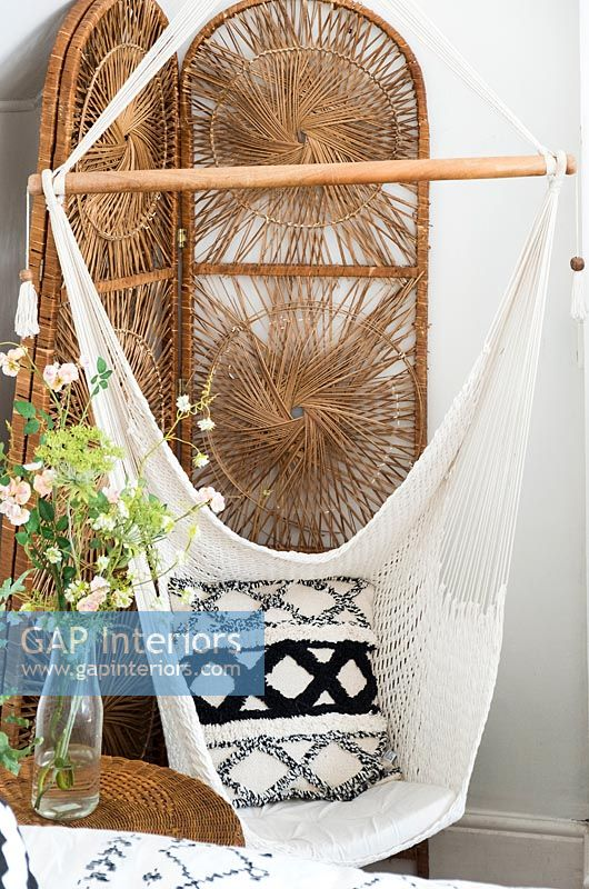 Macrame swing seat and wicker screen in country bedroom