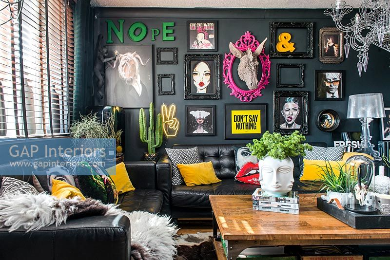 Eclectic living room with black painted walls and modern artworks