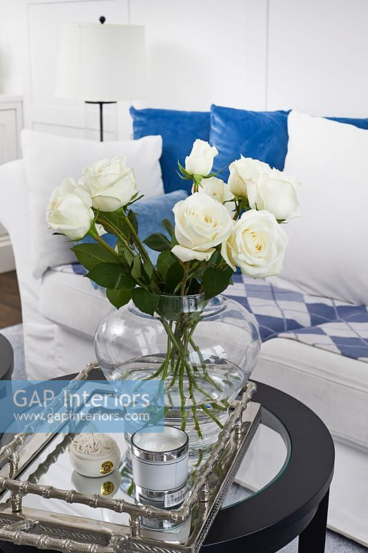 White roses in glass vase on silver tray