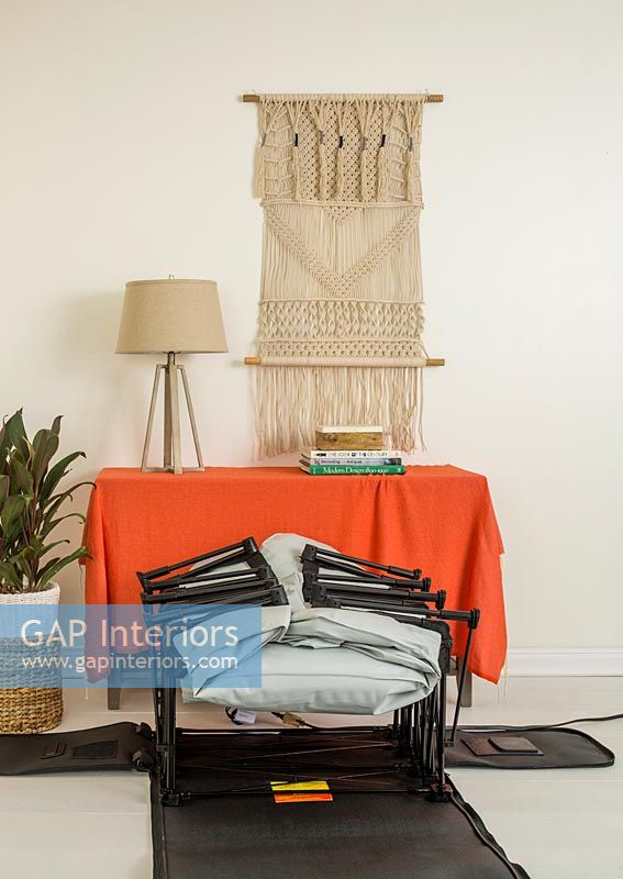 Orange blanket over sideboard with macrame wall hanging and folded bed