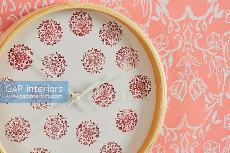 Decorative wall clock and colourful orange patterned wallpaper