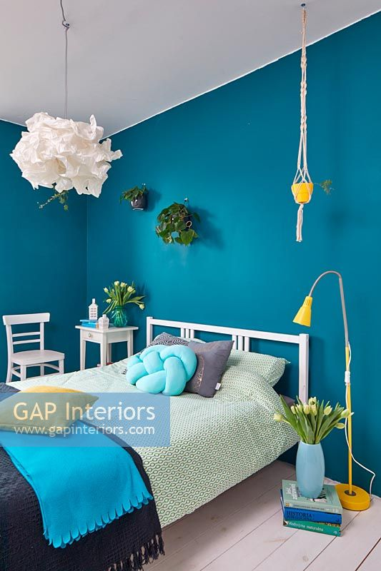 Modern bedroom with blue painted walls and spring flowers at Easter