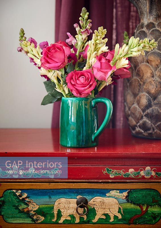 Colourful flower arrangement on decorative sideboard