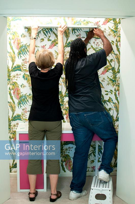 People wallpapering with tropical print wallpaper