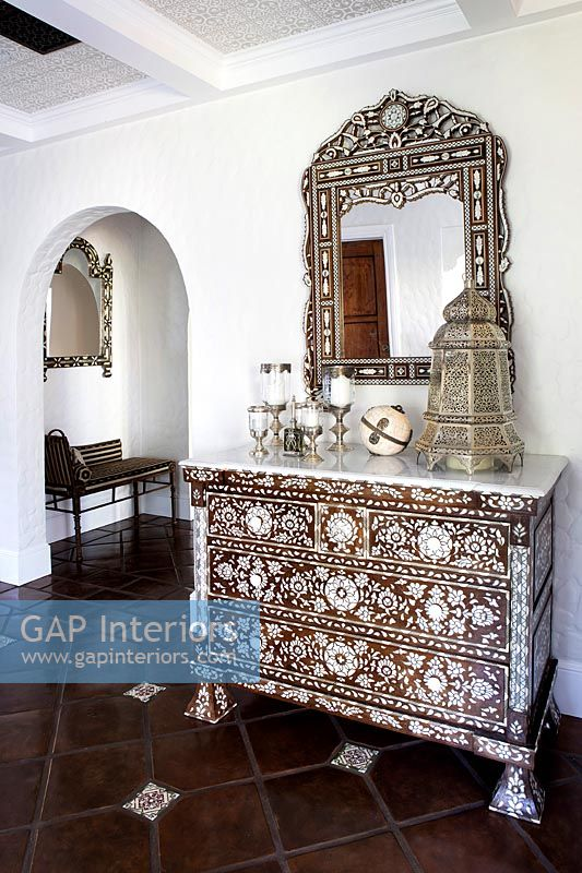 Ornate chest of drawers in country hallway