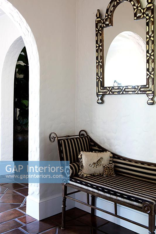 Striped recliner and ornate mirror in country hallway
