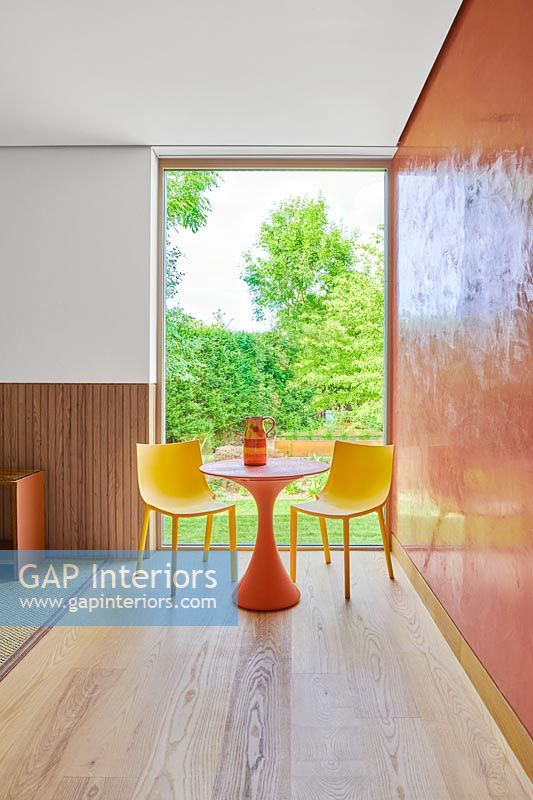 Orange table and yellow chairs next to orange wall