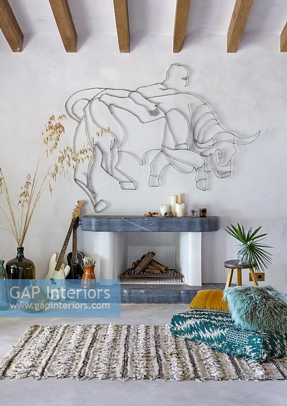 Fireplace with Bull sculpture on wall, guitars and rug - modern country living room