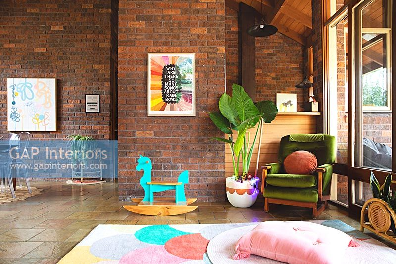 Toys in large modern living room with exposed brick walls and stone flooring