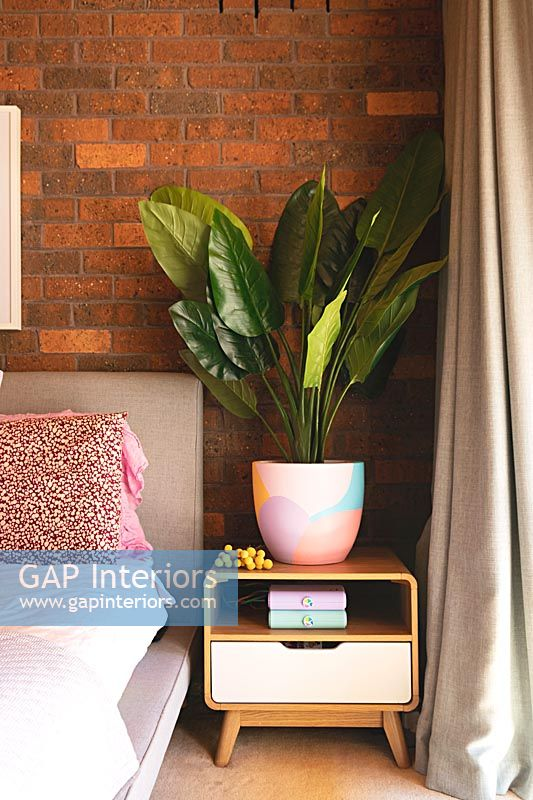 Large houseplant on retro bedside table