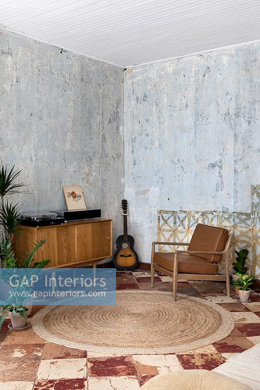 Living room with vintage furniture and bare plaster walls