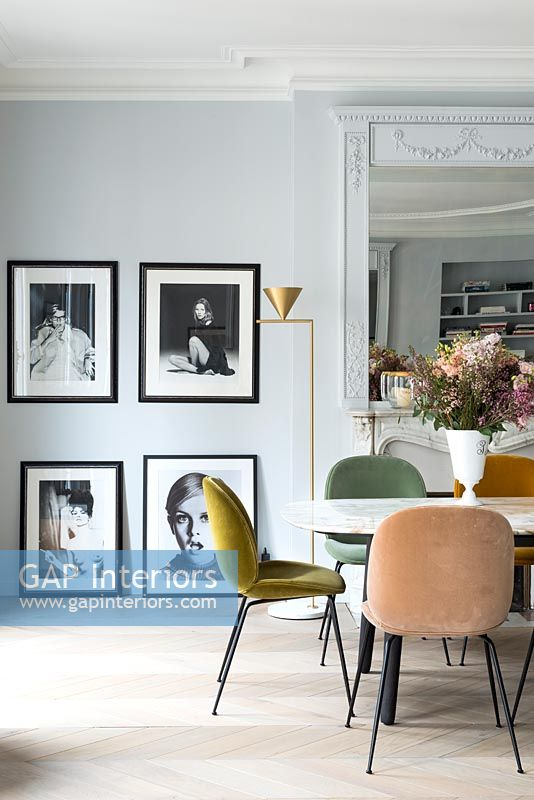 Framed black and white photographs in dining room with vintage furniture