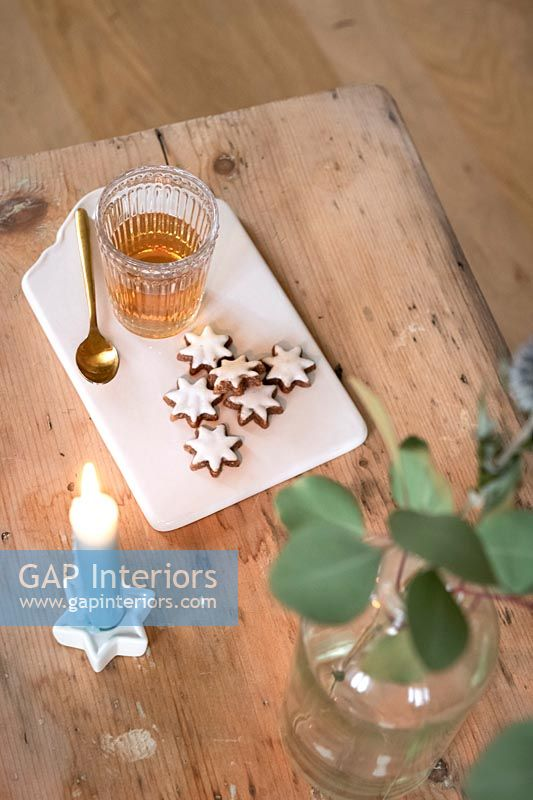 Detail of Christmas star biscuits, drink and candle on wooden table
