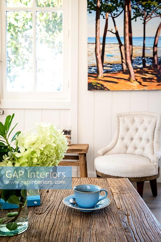 Cup and saucer wooden coffee table with colourful painting on wall