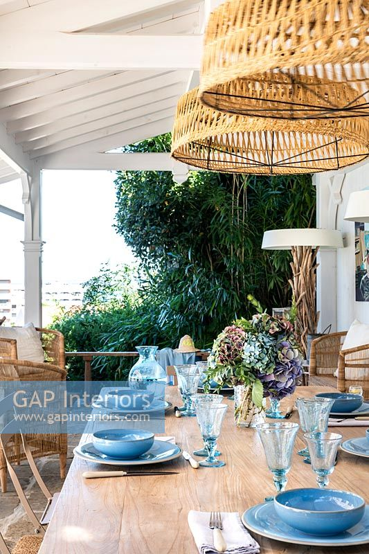 Blue crockery and glassware on outdoor dining table