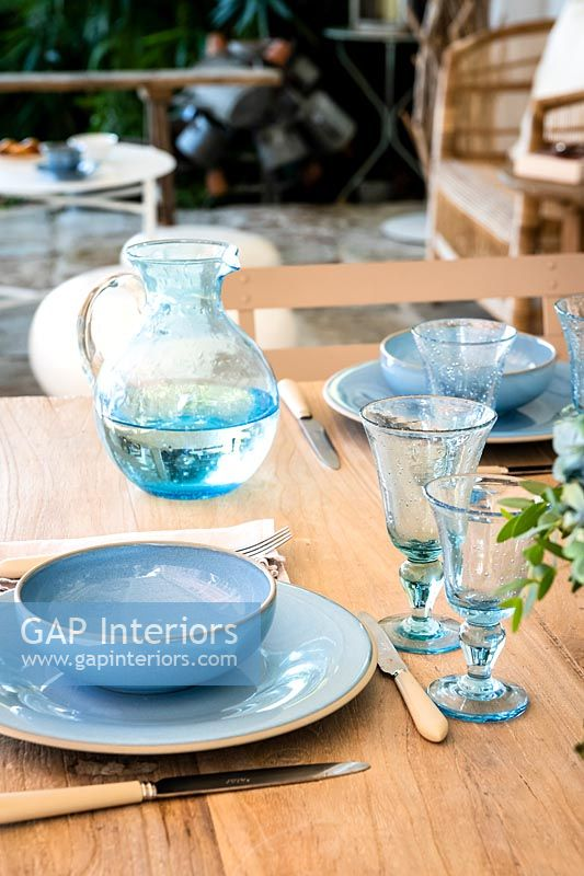 Detail of blue crockery and glassware on outdoor dining table