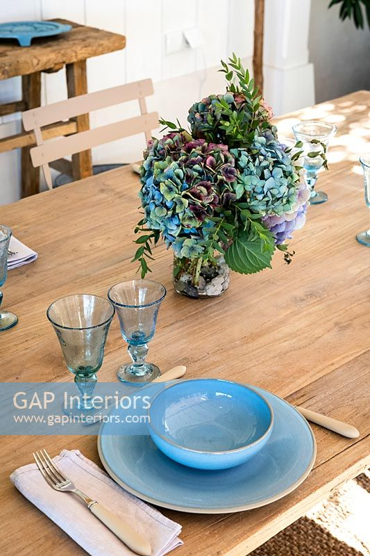 Flower arrangement on outdoor dining table set for lunch