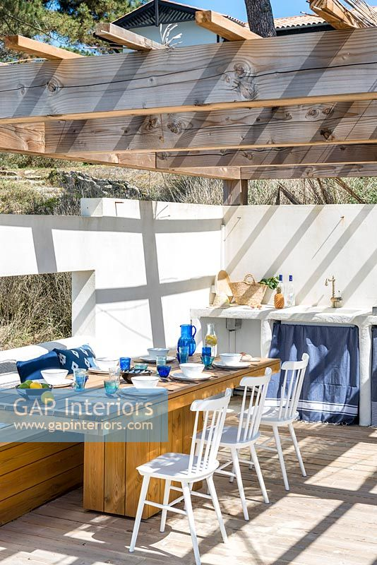 Walled dining area with outdoor kitchen on beach side terrace