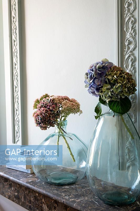 Cut flowers in large glass vases on marble mantelpiece
