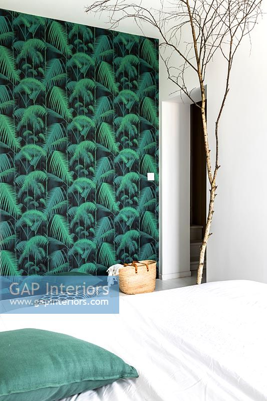 Green wallpapered feature wall and bare tree branch ornament in modern bedroom
