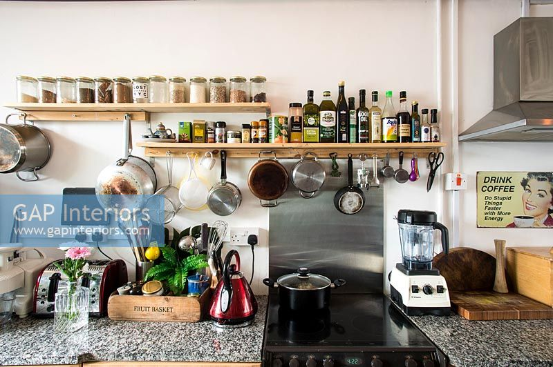 Modern kitchen with shelf of spices and cooking condiments