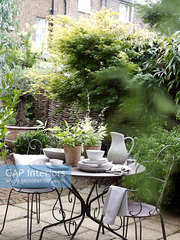 Small cafe style seating area in courtyard garden