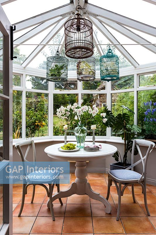 Decorative bird cages above small cafe table and chairs in conservatory