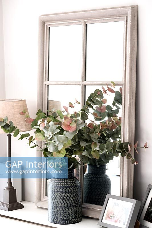 Vase of leaves and foliage on radiator cover with mirror