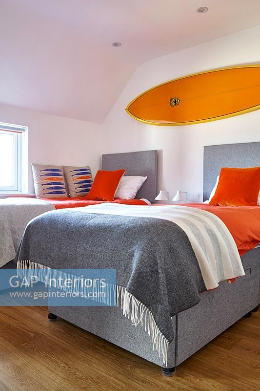 Bright orange surfboard above twin beds in modern bedroom