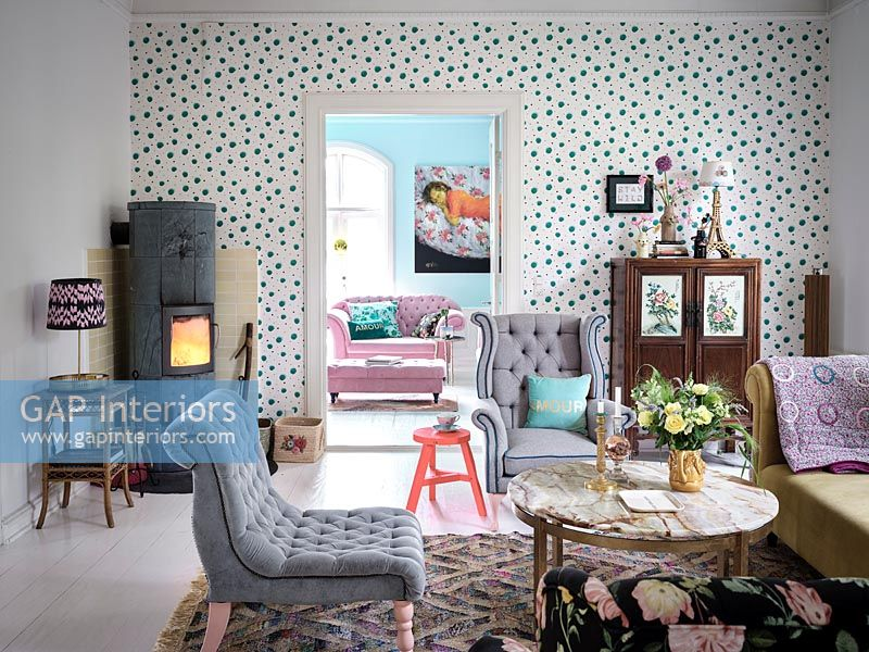 Spotty feature wall in eclectic living room with log burning stove